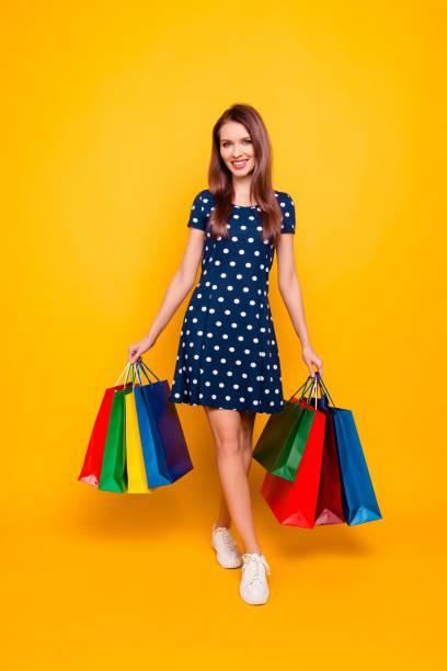 ganzkörper-porträt von sexy, hübsch, charmant, erfolgreich, selbstbewusst, professionelle mädchen, geht vom einkaufszentrum mit paketen in beiden händen, schritt mit bein, isoliert auf gelbem hintergrund - kleider günstig kaufen stock-fotos und bilder