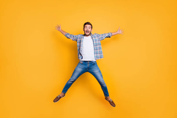 full-legh portrait of of crazy and excited handsome man jumping - mid air stock pictures, royalty-free photos & images