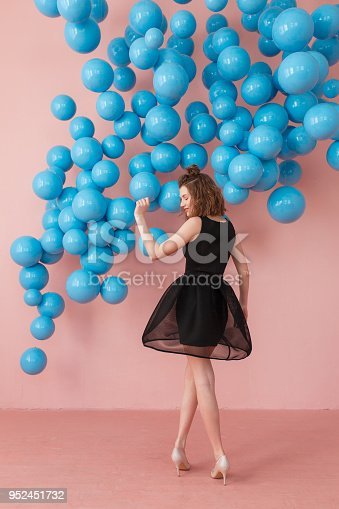 istock Full-lenght portrait of curious cheerful charming attractive woman with ideal hairdo and make up, she is thinking about the right choice and touching chin, isolated on bright pink background with blue balls hanging copyspace 952451732