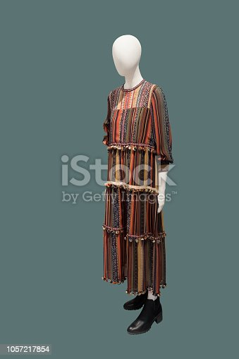 Full-length female mannequin wearing long colorful dress isolated. No brand names or copyright objects.