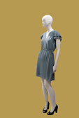 Full-length female mannequin wearing gray dress, isolated. No brand names or copyright objects.