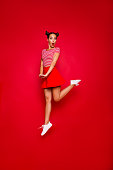 istock Full-length full-size vertical view of jumping and wondered brunette woman dressed in colourful bright clothes isolated on red background 1033726722