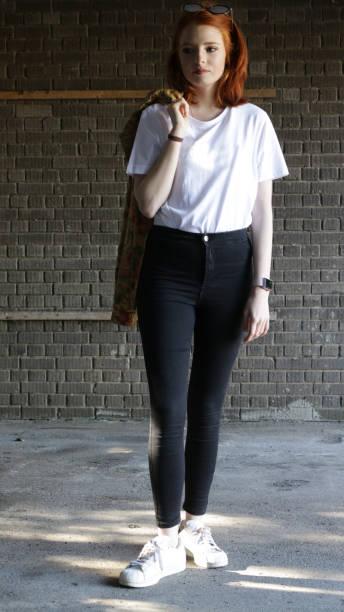 volledige afbeelding van rood haired tiener meisje 14/15 met bleke huid en sproeten dragen zonnebril bovenop haar hoofd houden haar uit gezicht, wit t-shirt, hoog getailleerde zwarte jeans en jasje geslagen over schouder - zwarte spijkerbroek stockfoto's en -beelden