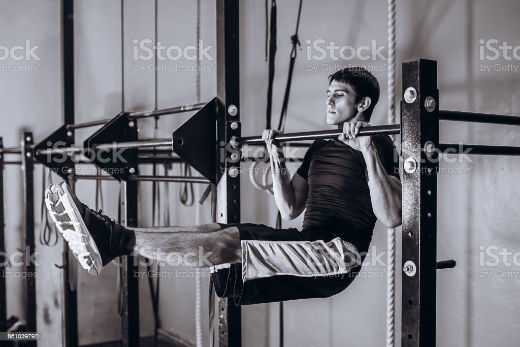 Cuerpo entero de hombre fuerte haciendo dominadas en una viga transversal - barra colgante Abs horizontal - foto de stock