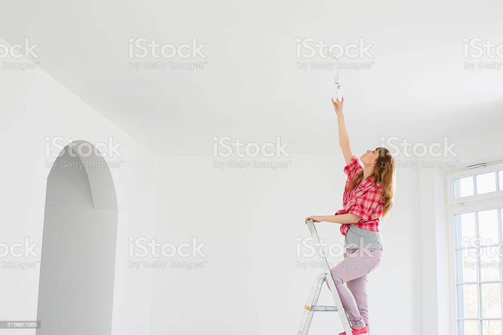 Full-length of woman on ladder fitting light bulb stock photo