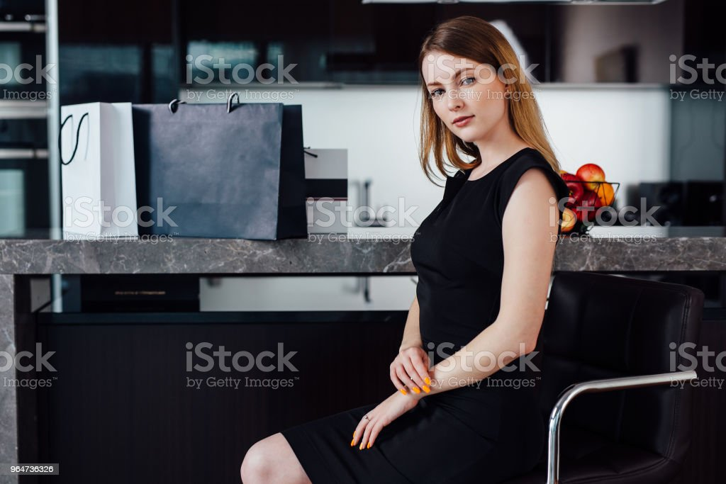 Full-length portrait of elegant woman with fair hair wearing black dress and high heels sitting on a bar chair in kitchen royalty-free stock photo