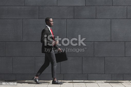 Full-length portrait of handsome African American entrepreneur walking on pavement with gray block wall in background, dressed in black suit, holding leather bag and coffee cup during break in work