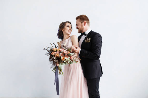 Full-length portrait of happy newlyweds. with bouquet. Isolated on white wall background isolated stock photo