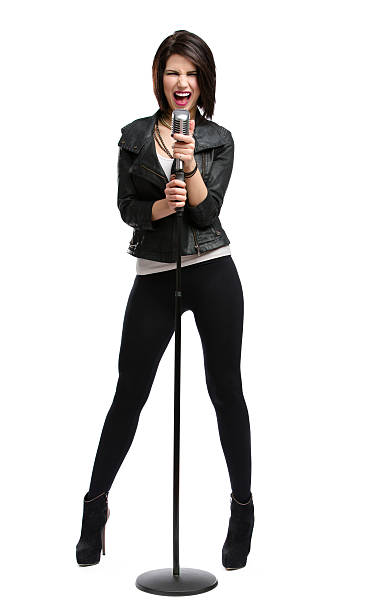 Full-length portrait of rock singer with mic Full-length portrait of rock singer wearing leather jacket and keeping static mic, isolated on white. Concept of rock music and rave singer stock pictures, royalty-free photos & images