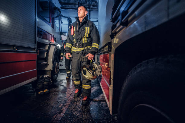 full-length portrait of two brave firemen in protective uniform walking between two fire engines in the garage of the fire dept - dept stock pictures, royalty-free photos & images