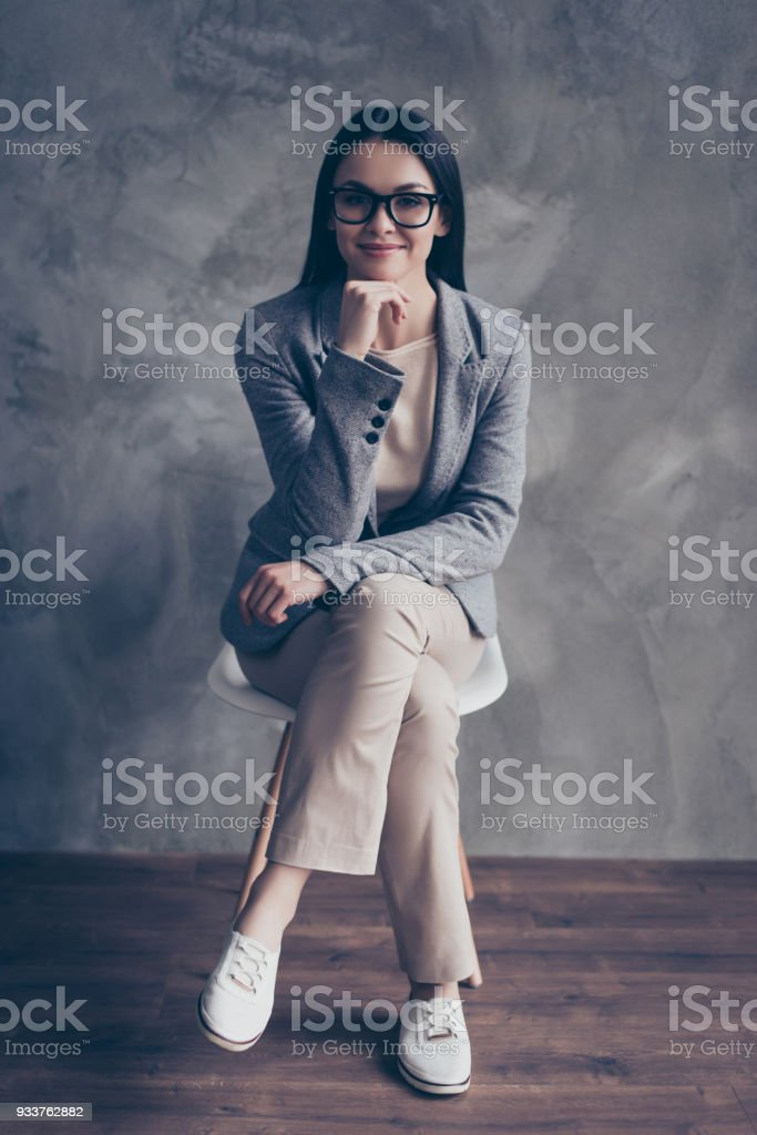 Full-length vertical portrait of confident charming pretty smart intelligent qualified friendly kind polite pensive lovely banker touching chin sitting chair isolated on gray concrete wall background stock photo