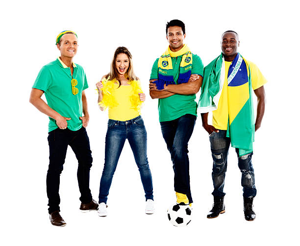 Full-length view of four happy Brazilian soccer supporters Four happy and confident-looking soccer fans in Brazilian colors, one with his foot on a soccer ball. fan club stock pictures, royalty-free photos & images