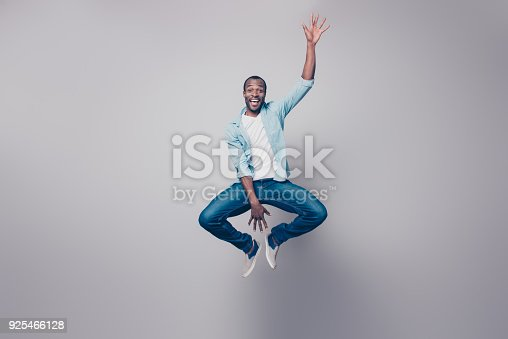 istock Full-size full-length portrait of cheerful handsome joyful excited delightful impressed surprised afro guy wearing casual denim jeans clothing jumping up, isolated on gray background 925466128