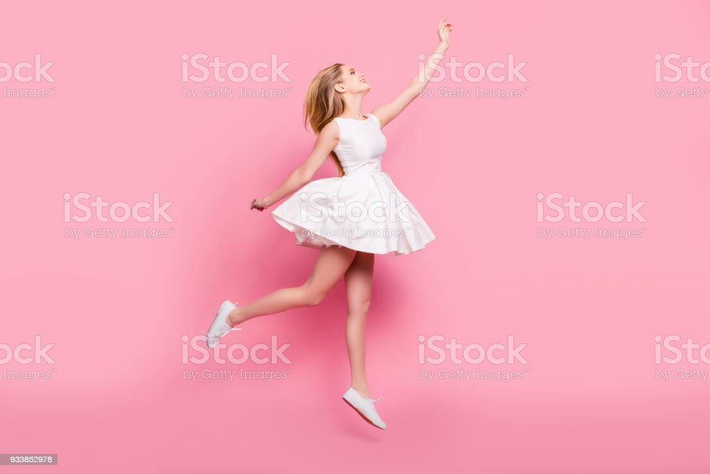 Full-size full-length side view portrait of beautiful attractive carefree tender gentle innocent stylish excited cheerful girl jumping up wants to touch sky isolated on background copy-space foto stock royalty-free