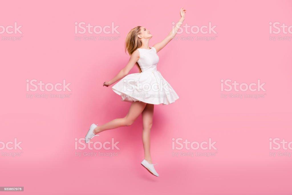 フルサイズ フルレングス サイドが美しい魅力的な屈託のない入札優しい無邪気なスタイリッシュな興奮して陽気な少女背景コピー領域に分離された空をタッチしたいジャンプの肖像画を表示します。 ストックフォト
