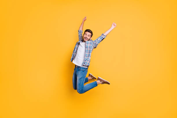 Full-size portrait of happy excited young man screaming and jumping up with raised fists celebrate the victory isolated on vivid yellow background Full-size portrait of happy excited young man screaming and jumping up with raised fists celebrate the victory isolated on vivid yellow background jump shot stock pictures, royalty-free photos & images