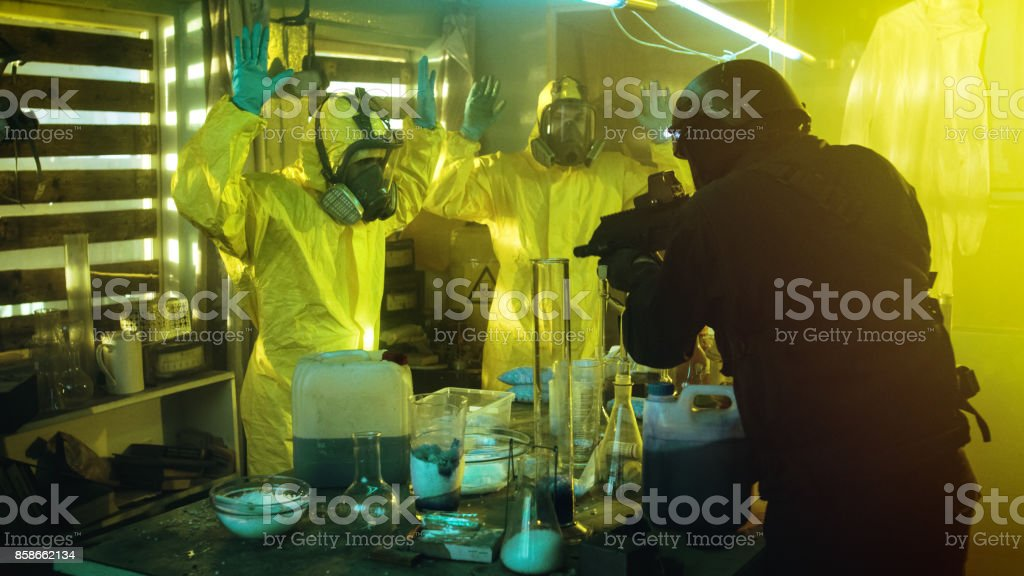 Fully Armed Special Anti-Narcotics Task Forces Soldier Arrests Two Clandestine Chemists Working in the Drug Producing Underground Laboratory. A lot of Drug Production Equipment is Lying around. stock photo
