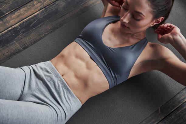 Voll konzentriert. Top-Ansicht von Mädchen mit schlanken Körper arbeitet auf dem Bauch, wenn auf dem Boden liegen – Foto