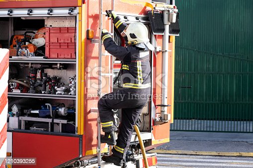 istock fully equipped fireman climbing the ladder of a fire truck 1210393255