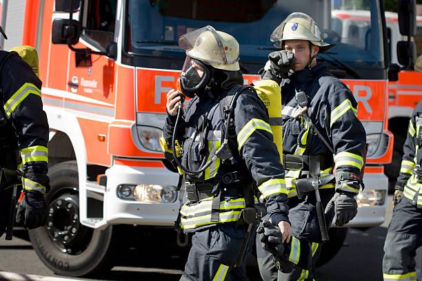 voll ausgestattete deutsche firefighters - feuerwehrmann deutsch stock-fotos und bilder