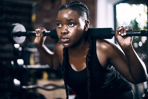 Full length shot of an attractive young female athlete lifting weights in the gym