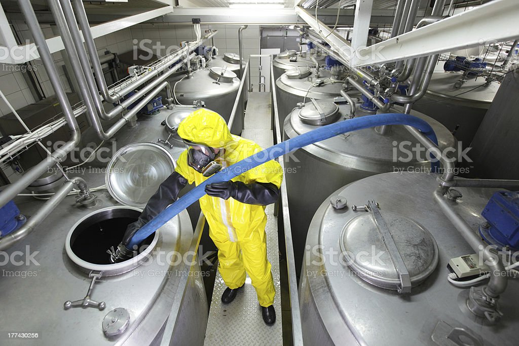 fully protected technician filling large silver tank in factory stock photo