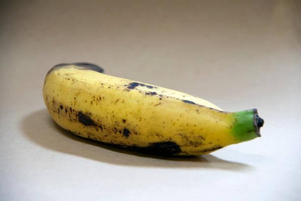 completamente madura de un plátano aislado sobre fondo marrón. - gangrena fotografías e imágenes de stock