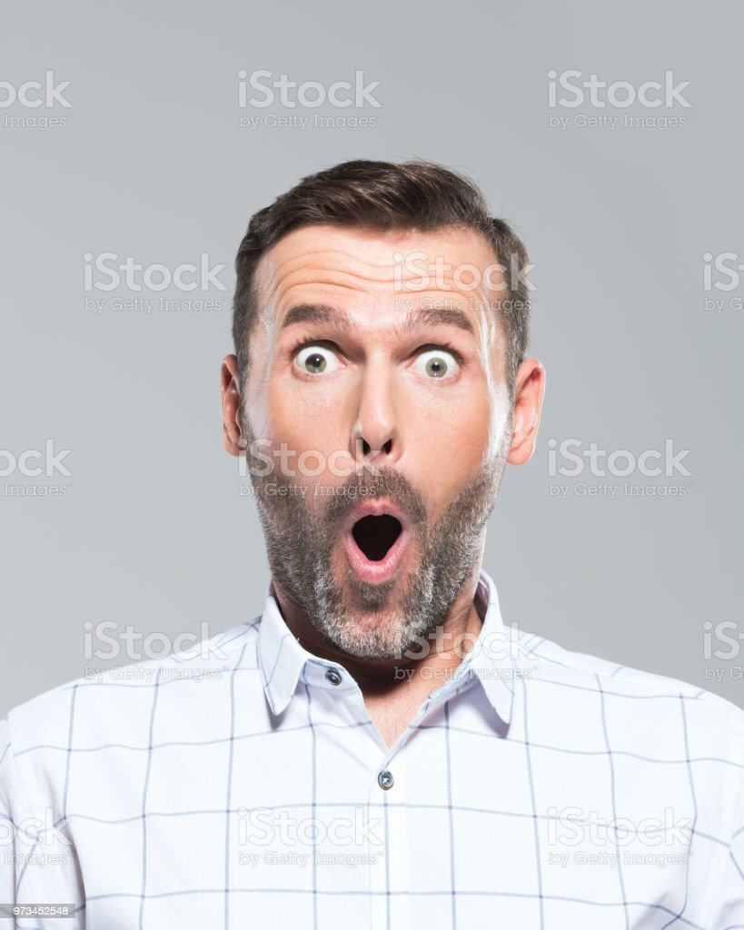 Fully surprised mature man Headshot of mature man with mouth open looking surprised. Excited mid adult man on grey background 30-39 Years Stock Photo