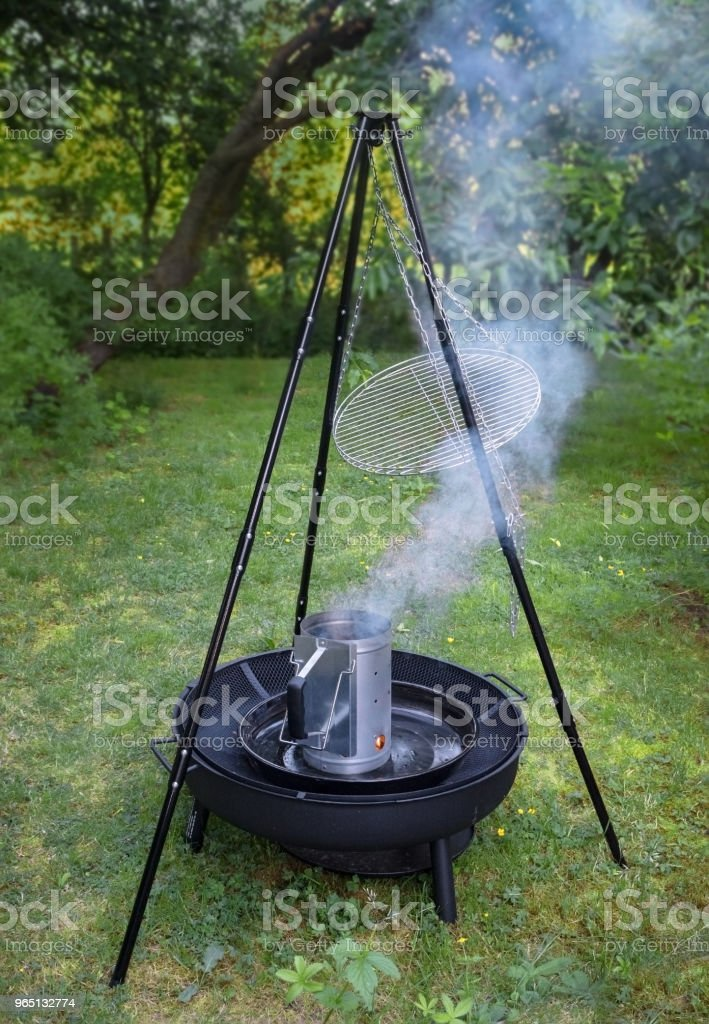 fuming barbecue charcoal chimney starter on a black tripod swivel grill in the garden zbiór zdjęć royalty-free