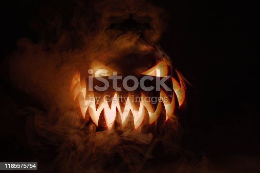 Fuming bright Jack-o'-lantern pumpkin on dark solid background. Glowing eyes and a terrible grin. Halloween minimal concept. Copy space. Desktop wallpapers
