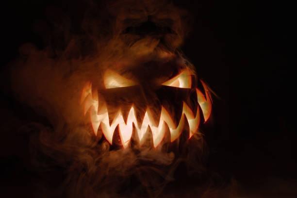 fuming jasne jack-o'-lantern dyni na ciemnym stałym tle. świecące oczy i straszny uśmiech. halloween minimalna koncepcja. kopiuj miejsce. tapety na pulpit - upiorny zdjęcia i obrazy z banku zdjęć