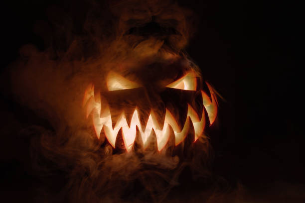 fuming bright jack-o'-lantern pumpkin on dark solid background. glowing eyes and a terrible grin. halloween minimal concept. copy space. desktop wallpapers - orrore foto e immagini stock