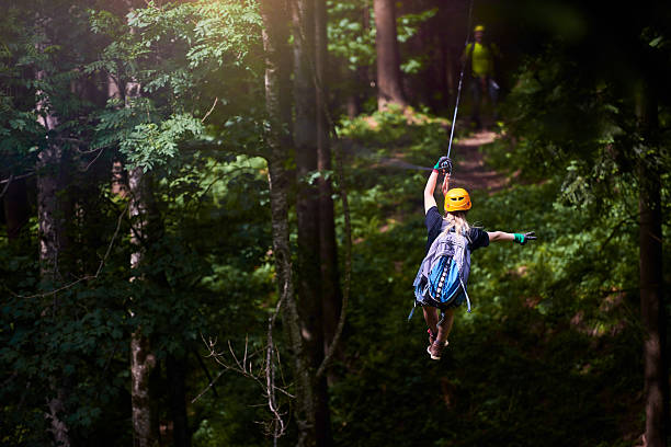 fun, adrenaline and adventure on the zip line rear view of woman in the forest with her backpacker enjoying adventure on tyrolean traverse. zip line stock pictures, royalty-free photos & images