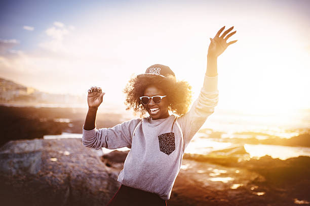Fun African American girl laughing and dancing at the beach stock photo