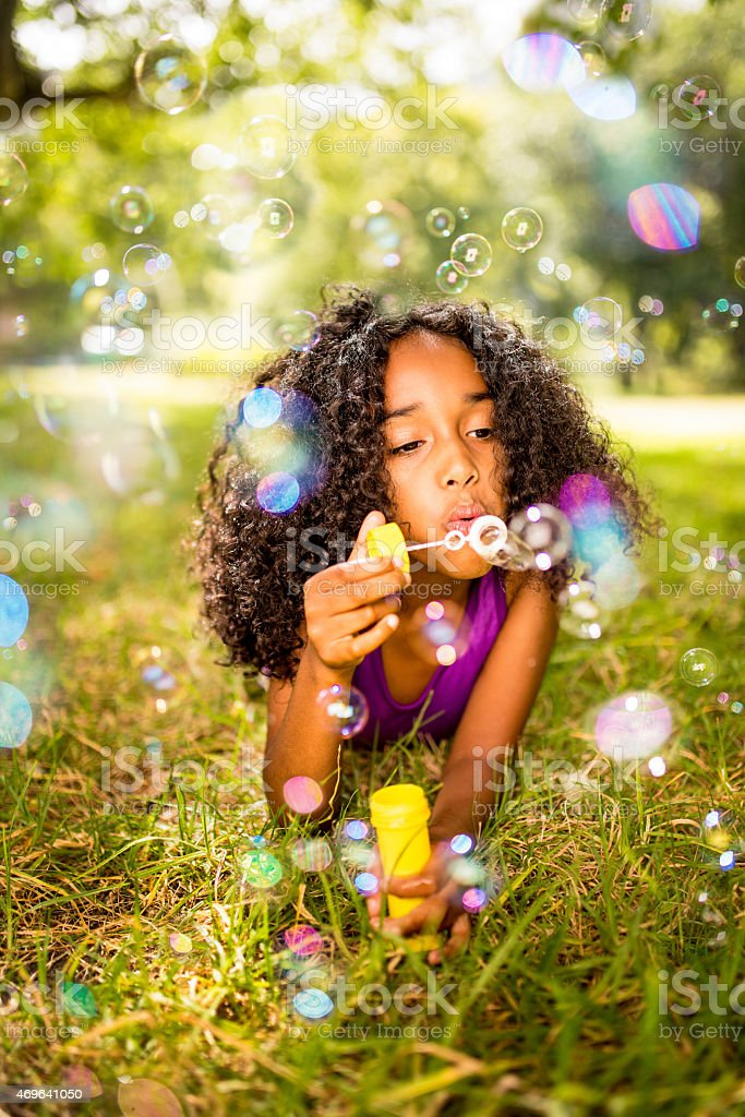 Fun Afro girl blowing bubbles in a park stock photo