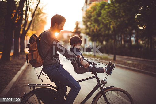 Father and his son cycling together outdoors on a beautiful sunny day