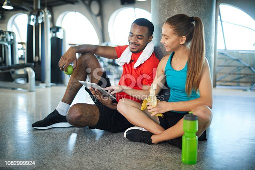 Young active man and woman having snack at break between workouts and watching online videos in tablet