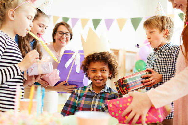 Fun Birthday Party Portrait of happy African-American boy receiving gifts surrounded by friends at Birthday party, copy space group of friends giving gifts to the birthday girl stock pictures, royalty-free photos & images