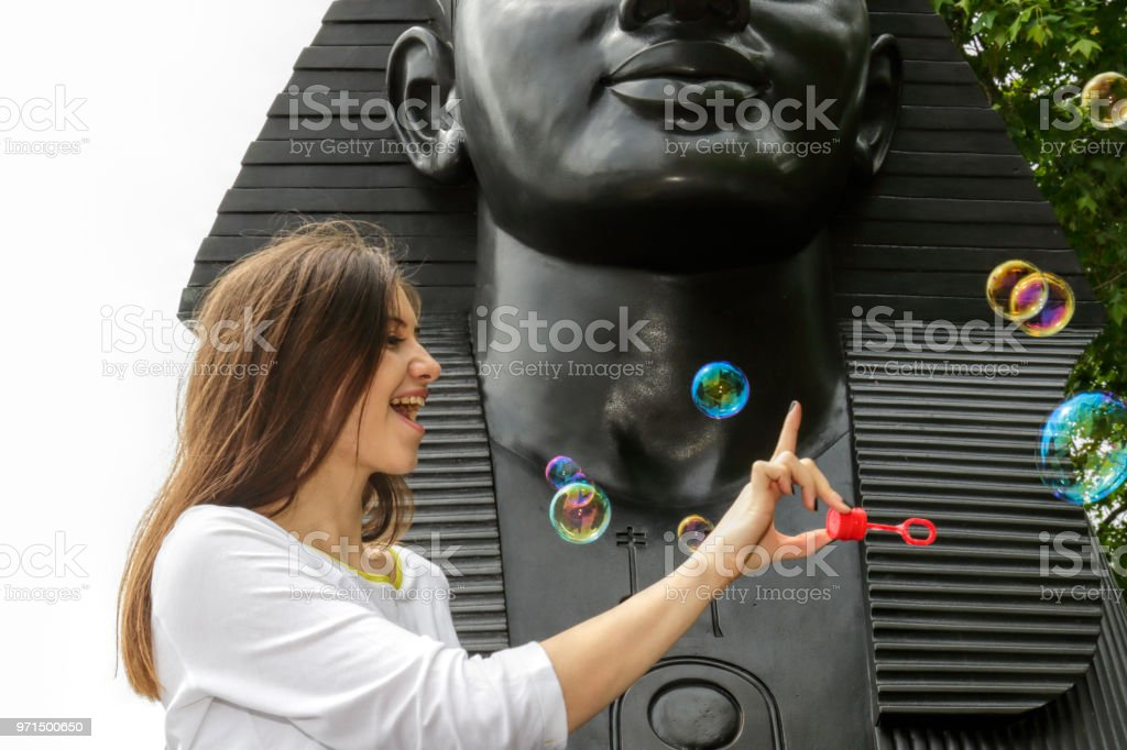 Fun blowing bubbles by a London Sphinx Bulgarian outdoor girl stock photo