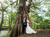 Fun bride and groom standing together and leaning on tree