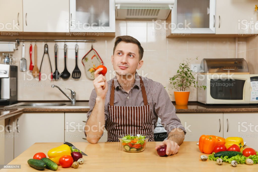 Fun caucasian young man in apron, brown shirt sitting at table, choosing between onion and tomato, cuting vegetable salad with knife in light kitchen. Dieting concept. Cooking at home. Prepare food. stock photo