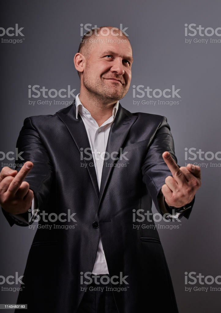 Fun comic bald business man in black suit showing the finger fuck sign on grey background. Closeup royalty-free stock photo