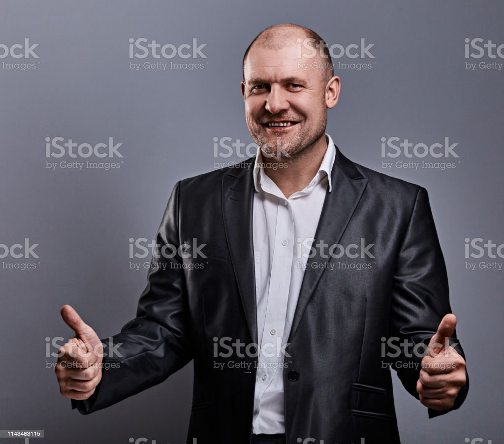 Fun comic bald business man in black suit showing the finger success thumb up sign on grey background. Closeup royalty-free stock photo