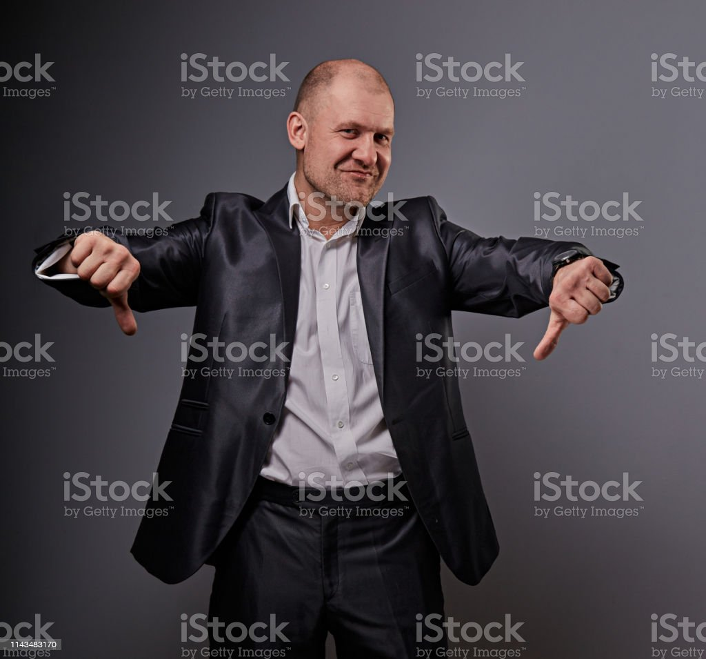 Fun comic bald business man in black suit showing the finger success thumb down sign on grey background. Closeup royalty-free stock photo