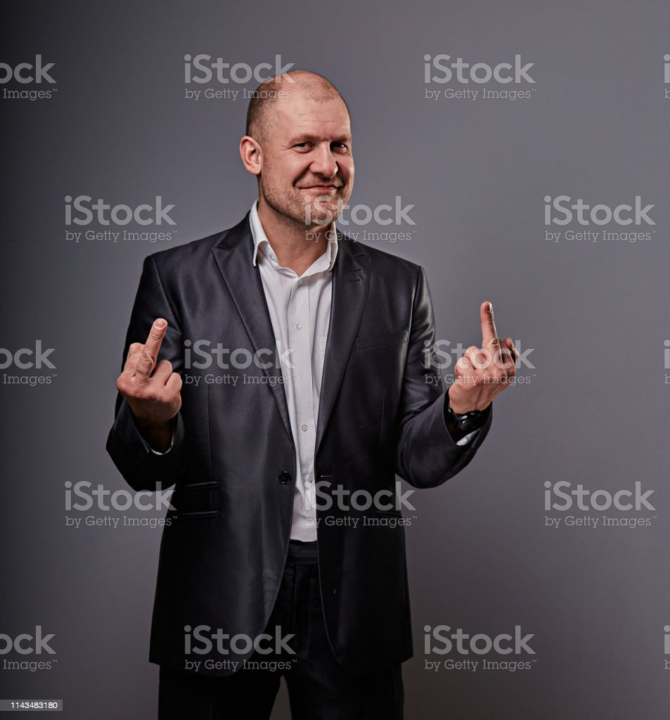 Fun comic smiling bald business man in black suit showing the finger fuck sign on grey background. Closeup royalty-free stock photo