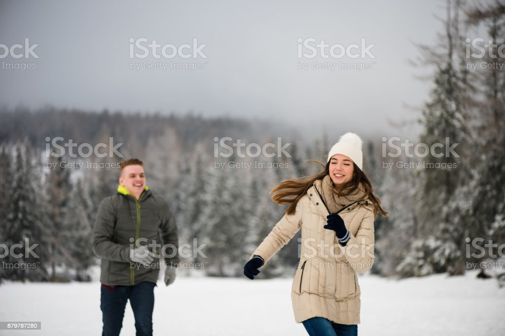 Fun couple playing in snow, running. stock photo