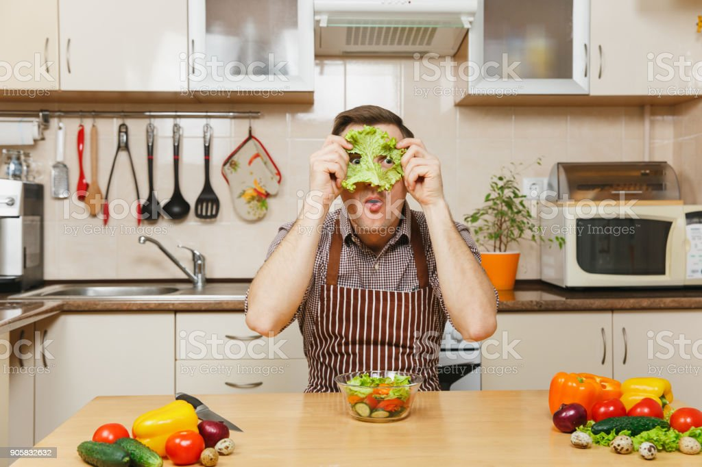 Fun crazy caucasian young man in apron, brown shirt sitting at table with vegetable salad, put green lettuce leaf on face like mask, in light kitchen. Dieting concept. Cooking at home. Prepare food. stock photo