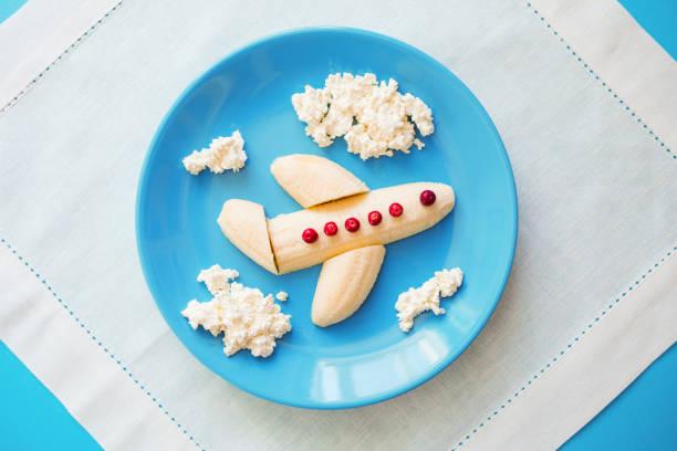fun food idee für kinder. kinderfrühstück: flugzeug gemacht von banane und wolken von quark auf eine blaue platte gemacht. träume vom fliegen. kreative mittagessen des künftigen piloten - dessert mit quark stock-fotos und bilder