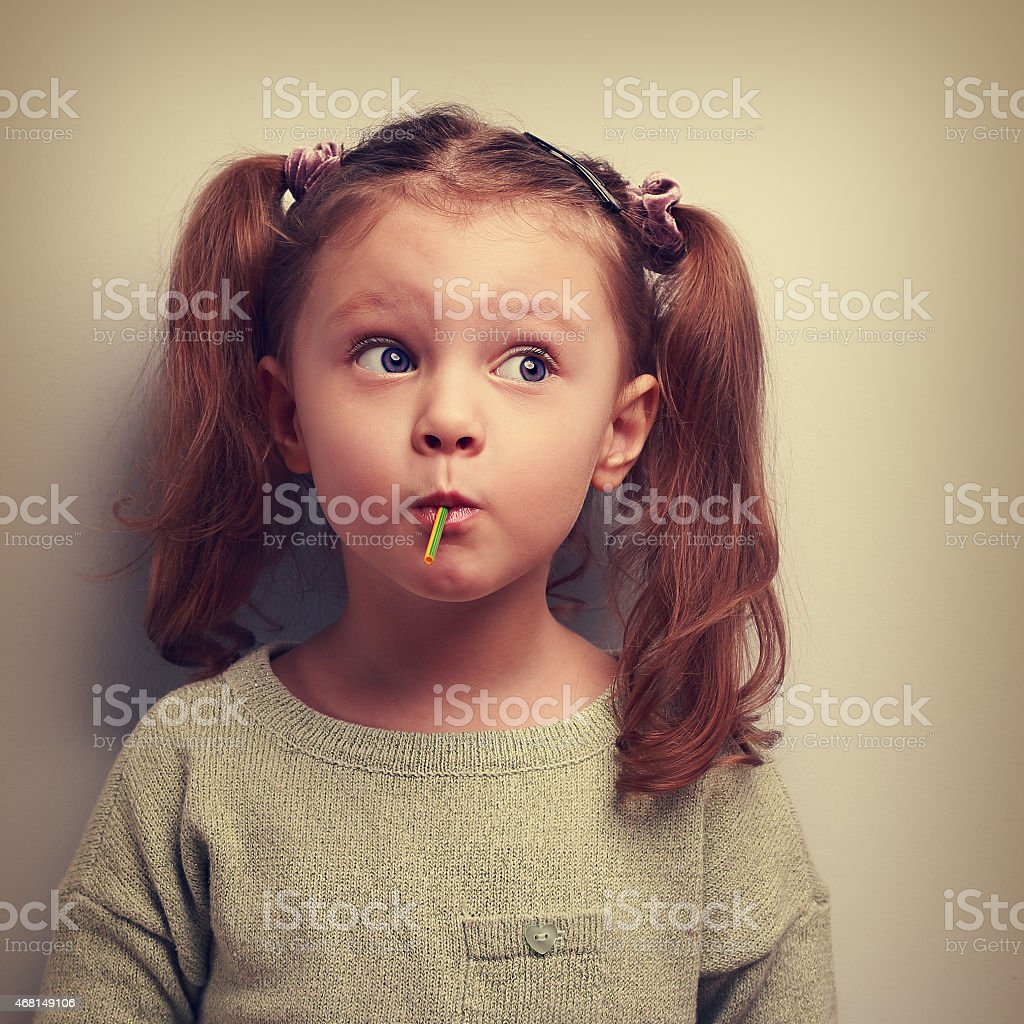Fun girl eating candy with surprising thinking big eyes. stock photo