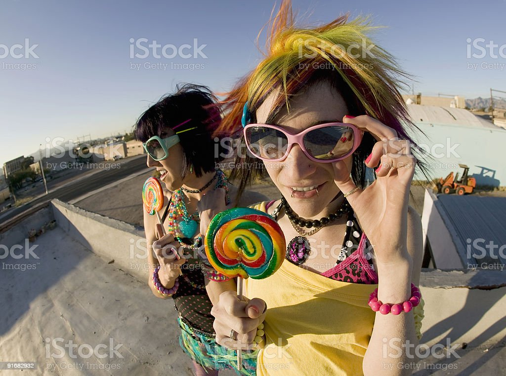 Fun girls on the roof with lollipops stock photo